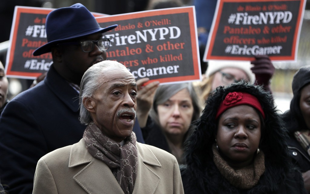 Rev. Al Sharpton, left, stands with activists while speaking during a news conference outside of New York Police headquarters, Thursday, Dec. 6, 2018,