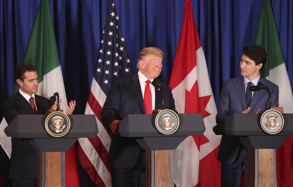 Flanked by Mexico's President Enrique Pena Nieto, left, and Canada's Prime Minister Justin Trudeau, President Donald Trump smiles during a signing cer