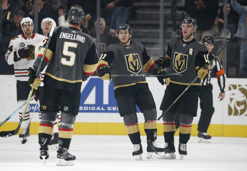 Vegas Golden Knights right wing Reilly Smith, right, and center Jonathan Marchessault, center, celebrate after defenseman Deryk Engelland (5) scored a