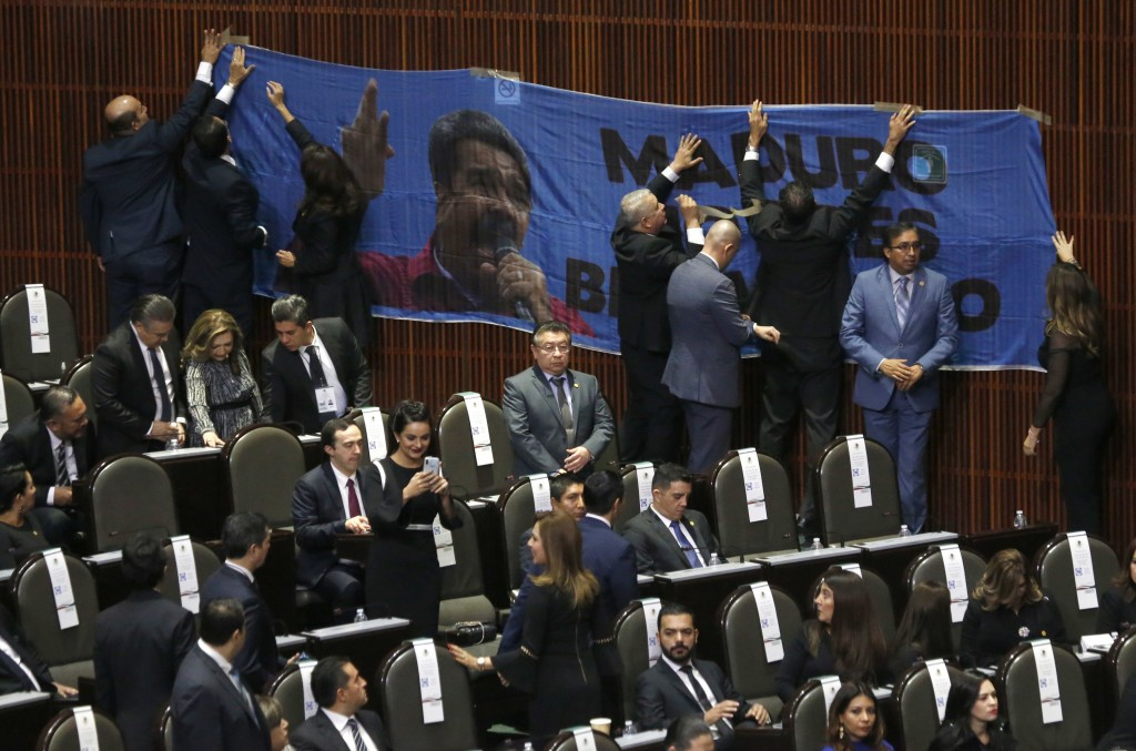 """Conservative legislators tape a banner with a message that reads in Spanish: """"(Nicolas) Maduro, you're not welcome"""" to a wall in the lower house of Co"""