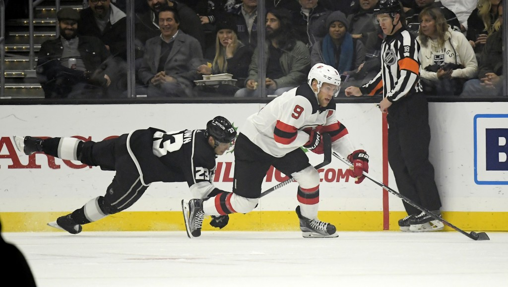 Los Angeles Kings right wing Dustin Brown, left, dives for the puck as New Jersey Devils left wing Taylor Hall takes it from him during the first peri