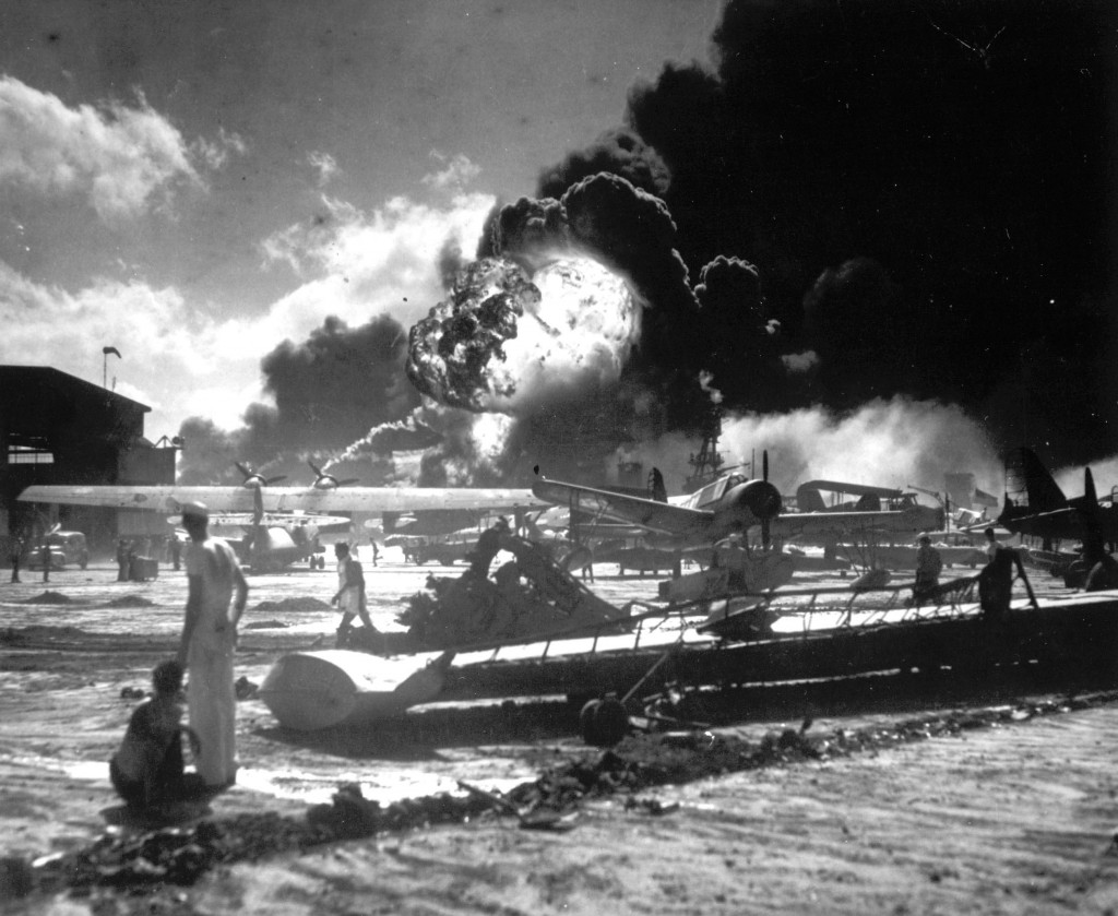 In this Dec. 7, 1941 file photo, sailors stand among wrecked airplanes at Ford Island Naval Air Station as they watch the explosion of the USS Shaw in
