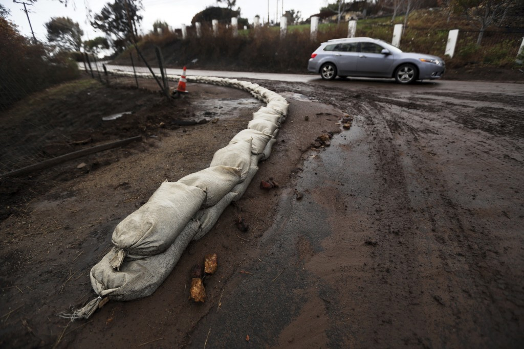 Sandbags help to control mud and debris flow in an area burned by the Woolsey Fire in Malibu, Calif. Thursday, Dec. 6, 2018. The second round of a fal