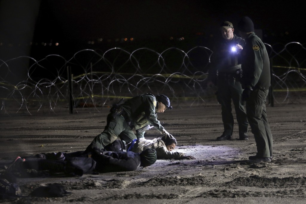 A U.S. Border Patrol agent pats down Honduran migrants after they crossed onto U.S territory from Tijuana, Mexico, on Friday, Nov. 30, 2018. Thousands