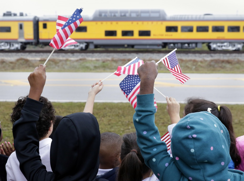 Students from Salyer Elementary School wave flags as the train carrying the body of former president George H.W. Bush travels past their school on the