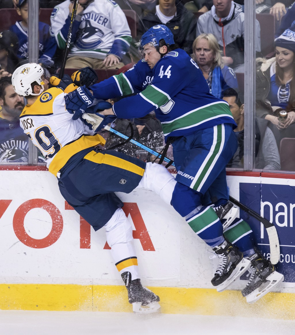 Vancouver Canucks' Erik Gudbranson, right, checks Nashville Predators' Roman Josi, of Switzerland, during the second period of an NHL hockey game Thur