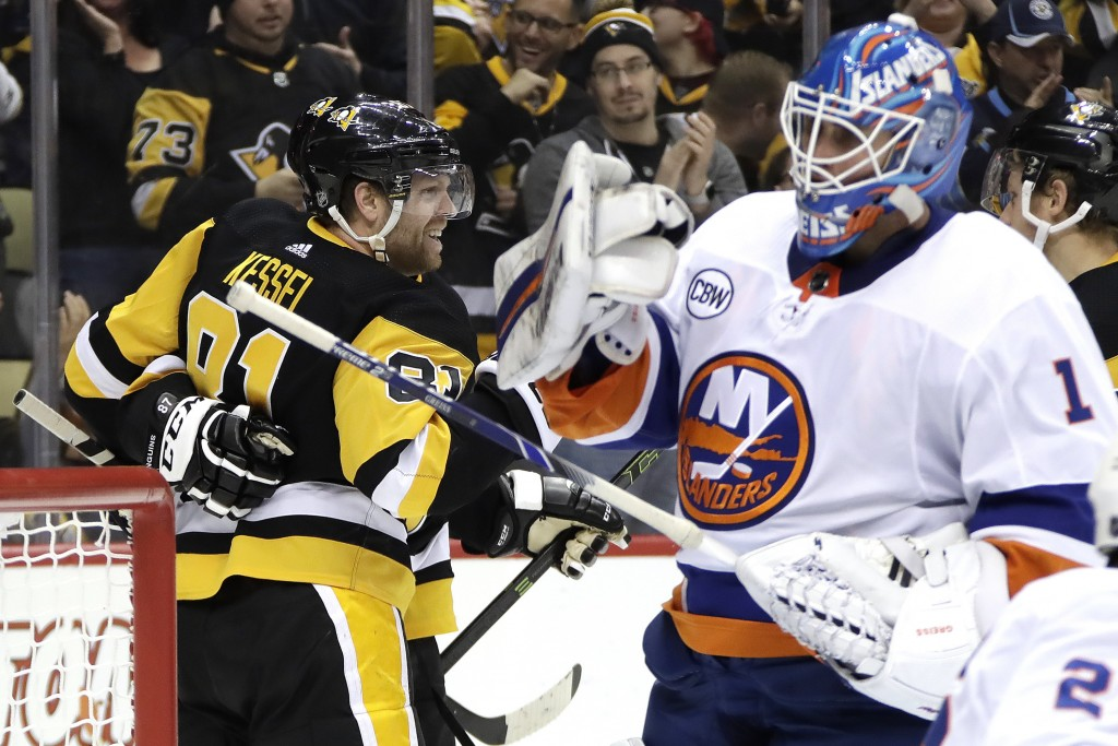 Pittsburgh Penguins' Phil Kessel (81) celebrates his first of two second-period goals as New York Islanders goaltender Thomas Greiss (1) looks on duri