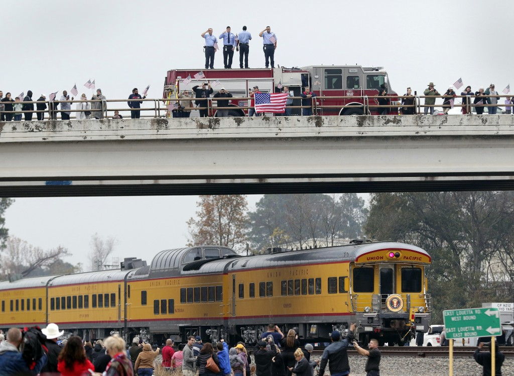 Firefighters stand on their truck and salute along with other attendants on an overpass as the train carrying the body of former president George H.W.