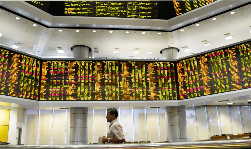 A visitor walks in front of private stock trading boards at a private stock market gallery in Kuala Lumpur, Malaysia, Friday, Dec. 7, 2018. Asian shar