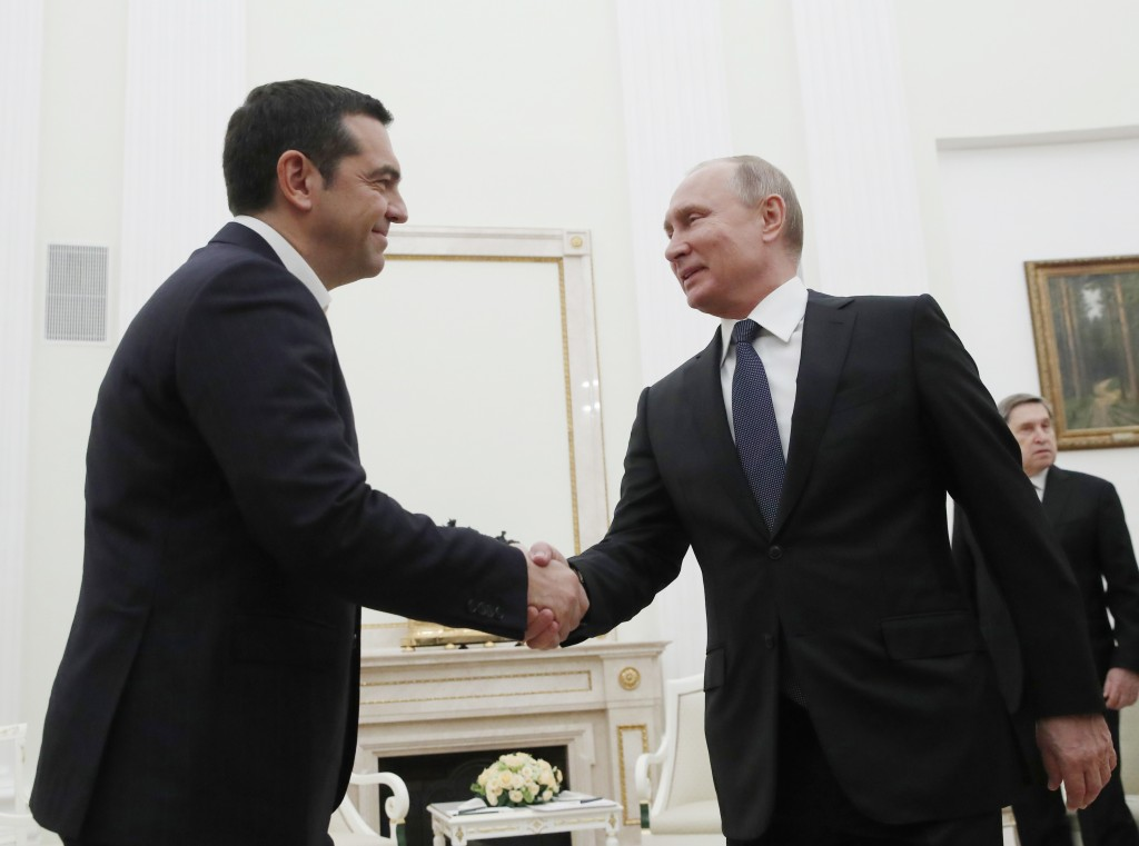 Greek Prime Minister Alexis Tsipras, left, and Russian President Vladimir Putin shake hands during their meeting in the Kremlin in Moscow, Russia, Fri