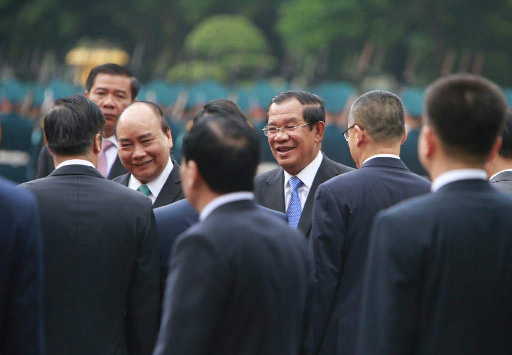 Vietnamese Prime Minister Nguyen Xuan Phuc, center left, introduces Vietnamese officials to Cambodian Prime Minister Hun Sen, center right, in Hanoi,