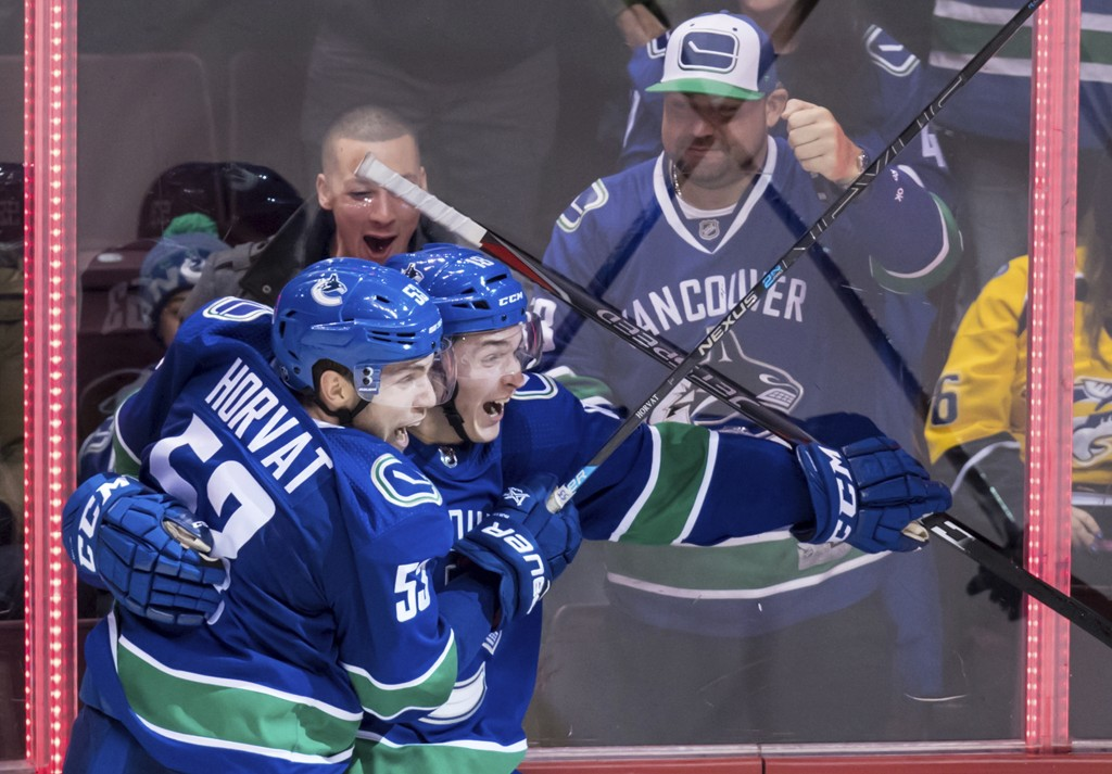 Vancouver Canucks' Bo Horvat, left, and Jake Virtanen celebrate Virtanen's goal against the Nashville Predators during the second period of an NHL hoc