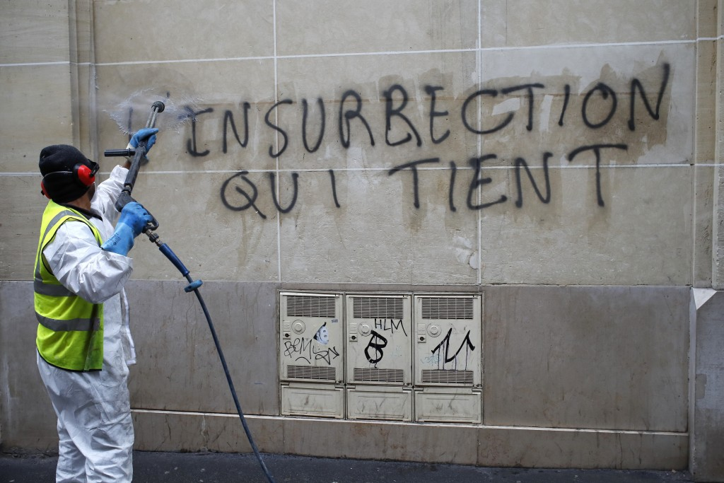 """A worker cleans a graffiti reading """"long term unrest"""" near the Champs-Elysees avenue, Friday, Dec. 7, 2018 in Paris. France was mobilizing tens of tho"""