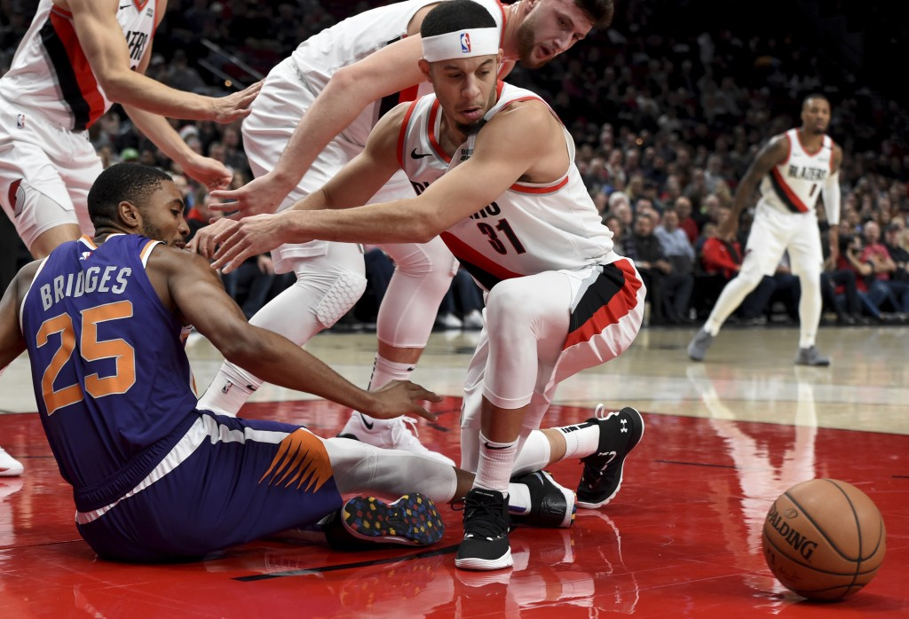 Phoenix Suns forward Mikal Bridges, left, and Portland Trail Blazers guard Seth Curry, right, battle for the ball during the first half of an NBA bask