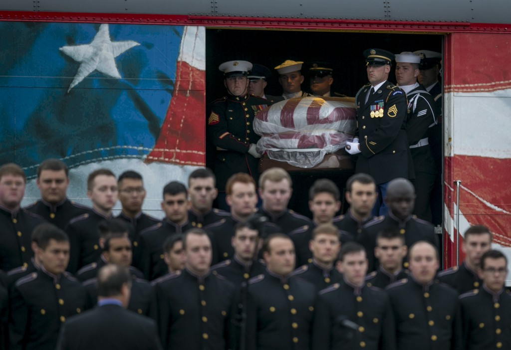 A joint military honor guard carries the casket of former President George H.W. Bush after it arrived by a presidential funeral train at Texas A&M Uni