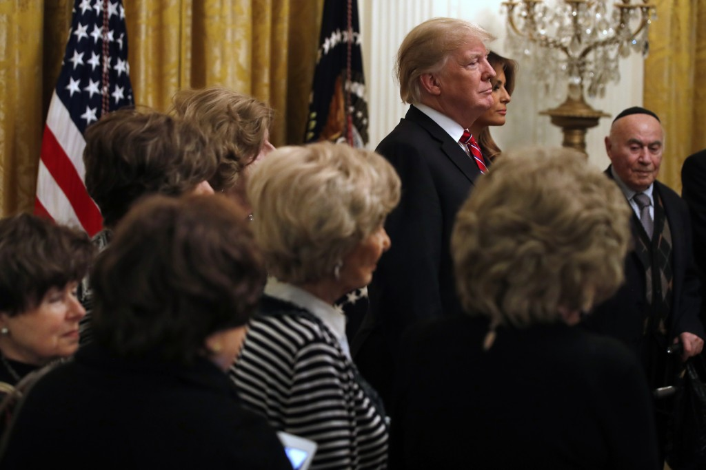 President Donald Trump and first lady Melania Trump are joined by Holocaust survivors, as they attend a Hanukkah reception, Thursday, Dec. 6, 2018, in