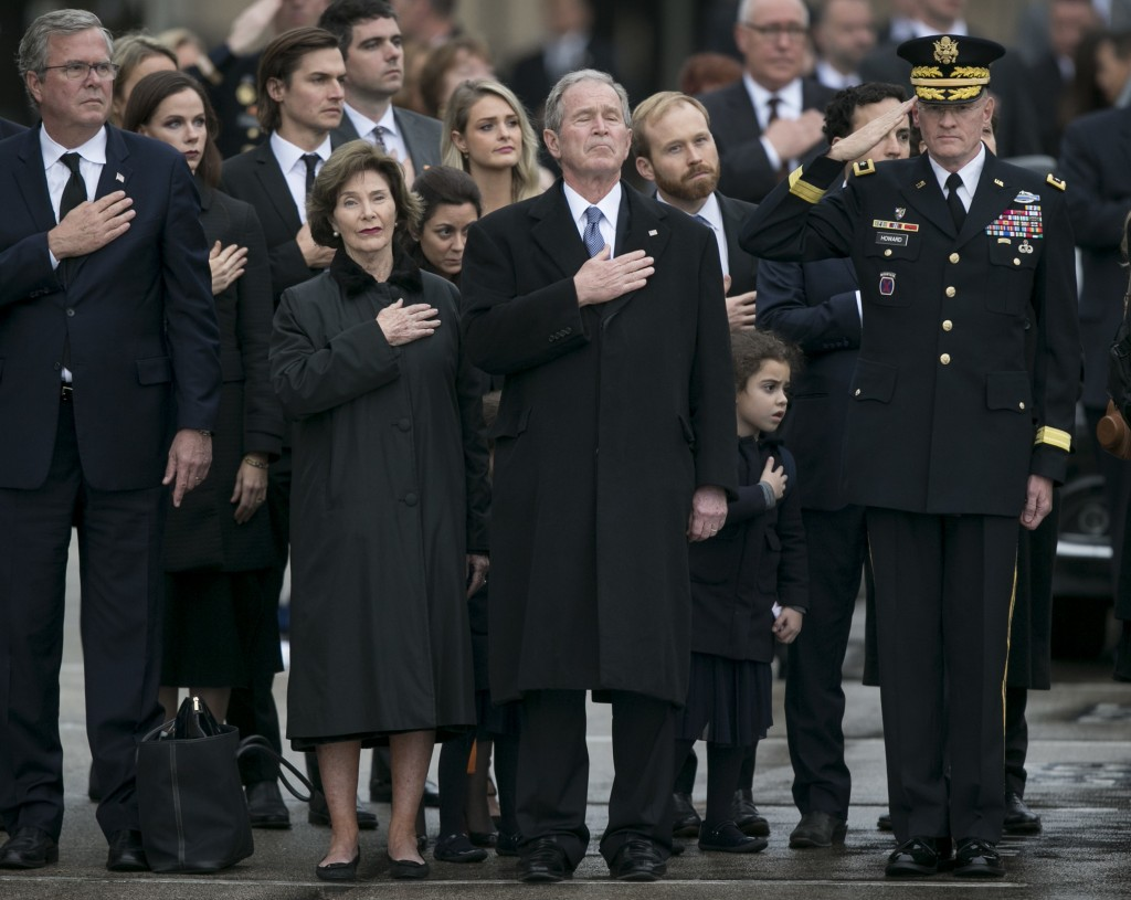 Former President George W. Bush, middle, with former first lady Laura Bush, covers his heart as the casket of his father, former President George H.W.