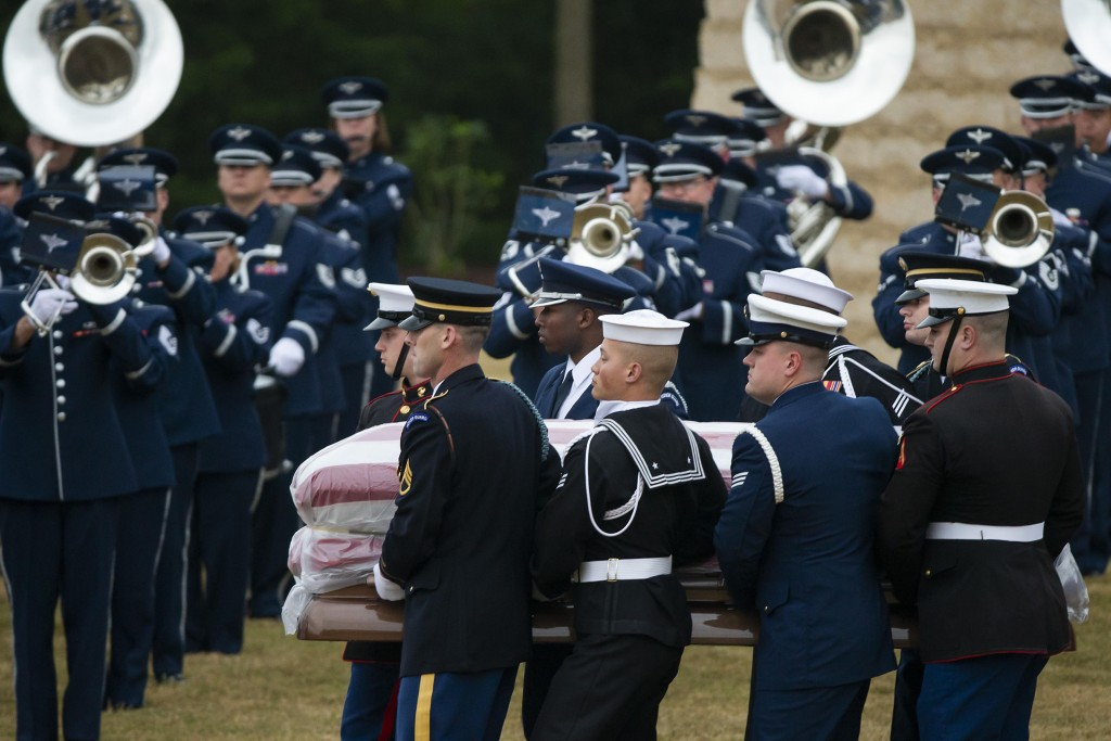 The flag-draped casket of former President George H.W. Bush is carried past a military band to a burial plot close to his presidential library for int