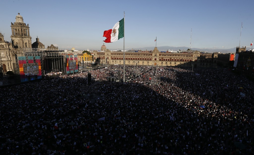 Flanked by the Metropolitan Cathedral, left, and the National Palace, people gather in the Zocalo to celebrate the country's newly sworn-in president,