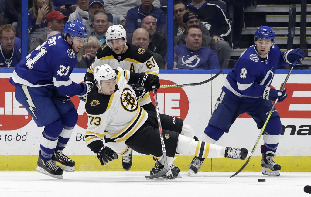 Tampa Bay Lightning center Brayden Point (21) takes down Boston Bruins defenseman Charlie McAvoy (73) during the first period of an NHL hockey game Th