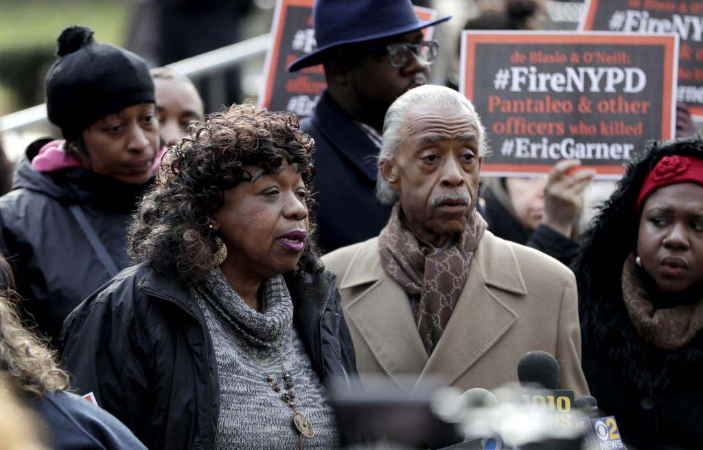 Gwen Carr, center, mother of Eric Garner, stands with Rev. Al Sharpton, right, during a news conference outside of New York Police headquarters, Thurs