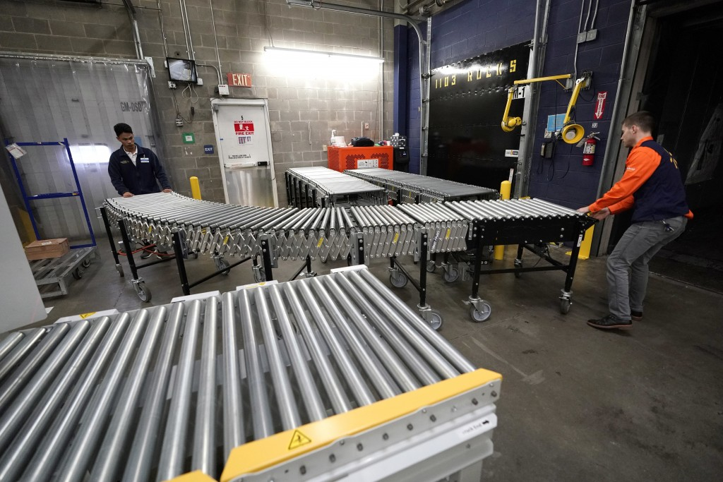 FILE- In this Nov. 9, 2018, file photo Laurence Marzo, left, and Ty Ford, right, move a conveyor belt into place to help unload a truck carrying merch