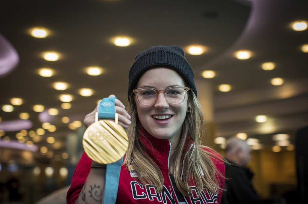 FILE - In this Feb. 26, 2018, file photo, freestyle skier Cassie Sharpe, of Canada, holds her 2018 Olympic gold medal after arriving from South Korea