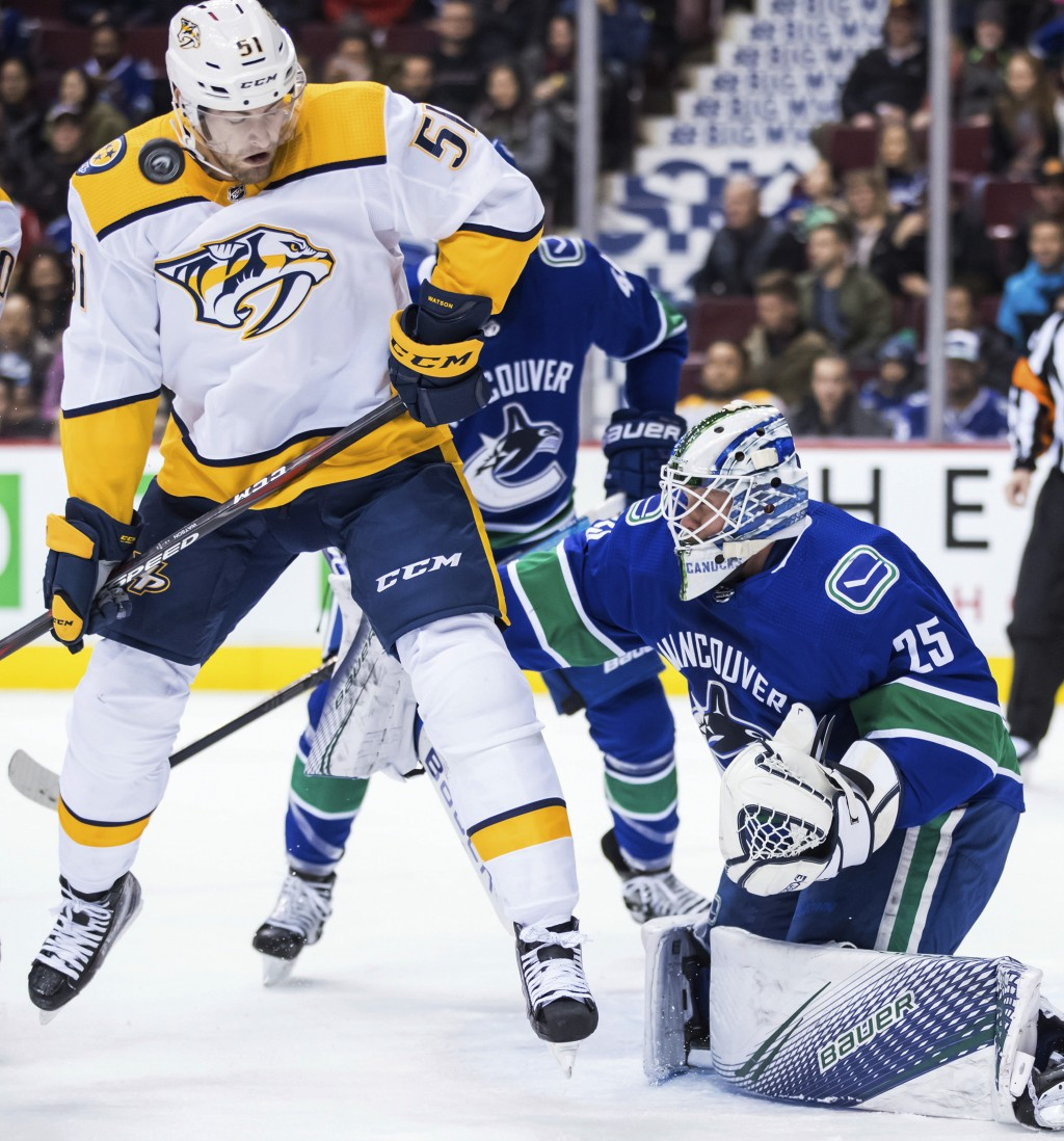 The puck bounces off Nashville Predators' Austin Watson (51) as he stands in front of Vancouver Canucks goalie Jacob Markstrom, of Sweden,during the f