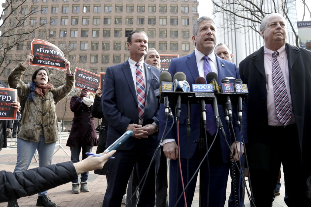 Protesters, left, chant as Patrolmen's Benevolent Association President Patrick Lynch, second from right, speaks during a news conference outside of p
