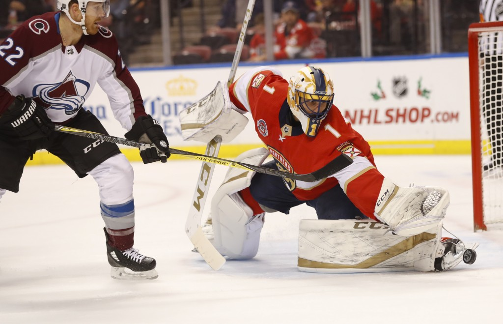 Florida Panthers goaltender Roberto Luongo (1) deflects a shot as Colorado Avalanche center Colin Wilson (22) looks on during the first period of an N