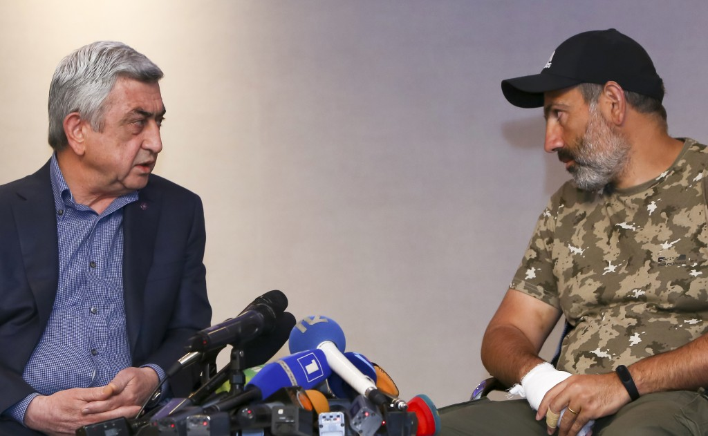 FILE - In this file photo taken on Sunday, April 22, 2018, Former Armenian President Serzh Sargsyan, left, speaks with protest leader Nikol Pashinian
