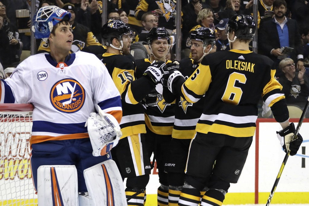 Pittsburgh Penguins' Riley Sheahan (15) celebrates his goal as New York Islanders goaltender Thomas Greiss (1) watches the replay on the scoreboard du