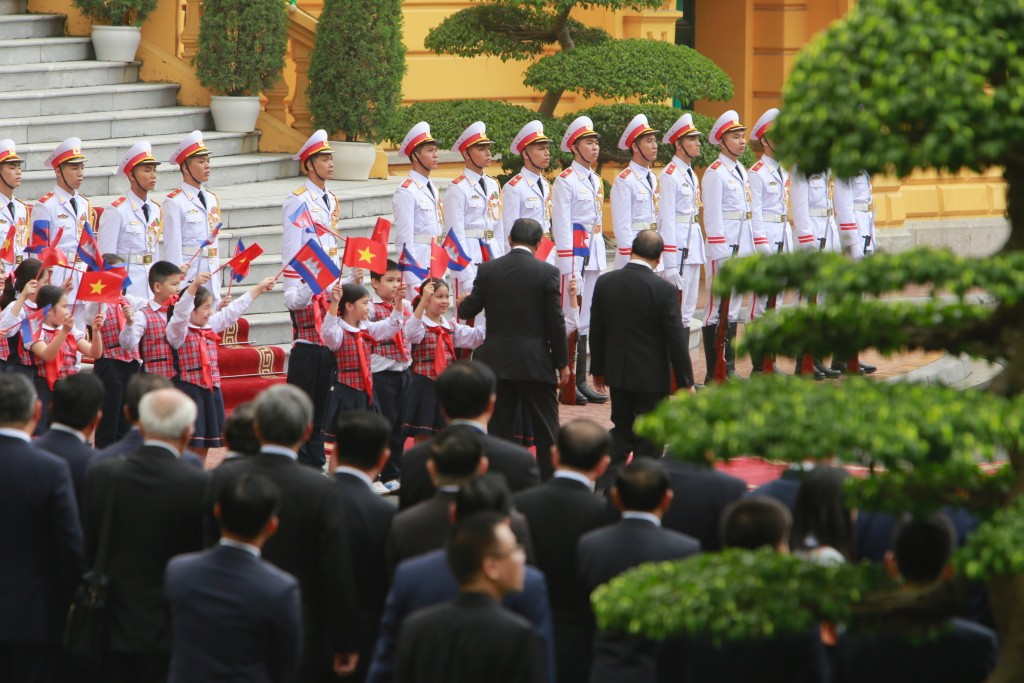 Cambodian Prime Minister Hun Sen, center lrgy, and his Vietnamese counterpart Nguyen Xuan Phuc, center right, are greeted by children in Hanoi, Vietna