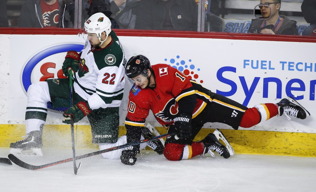 Minnesota Wild's Nino Niederreiter, left, of Switzerland, is checked by Calgary Flames' Derek Ryan during second-period NHL hockey game action in Calg