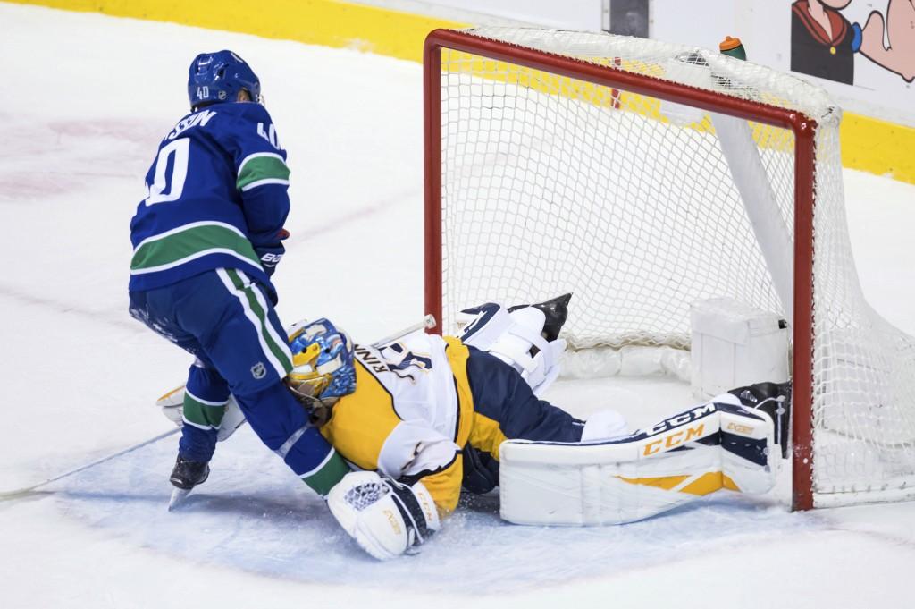 Vancouver Canucks' Elias Pettersson, left, of Sweden, scores on a penalty shot against Nashville Predators goalie Pekka Rinne, of Finland, during the