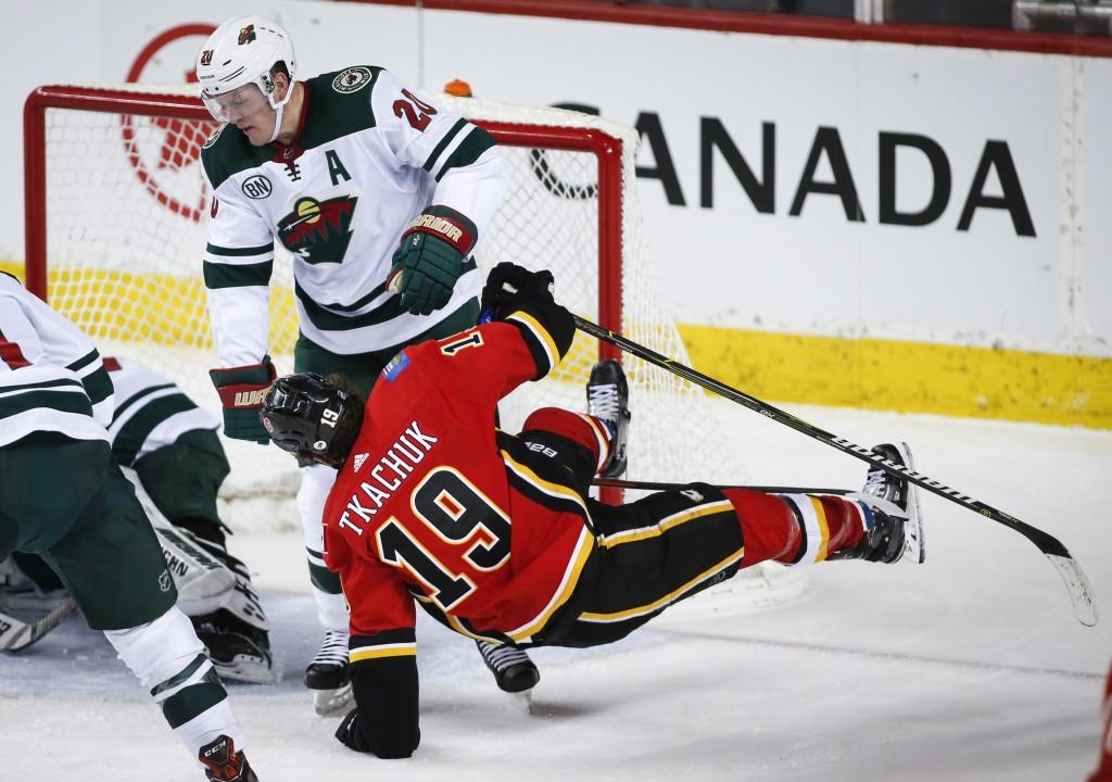 Minnesota Wild's Ryan Suter, left, sends Calgary Flames' Matthew Tkachuk to the ice during second-period NHL hockey game action in Calgary, Alberta, T