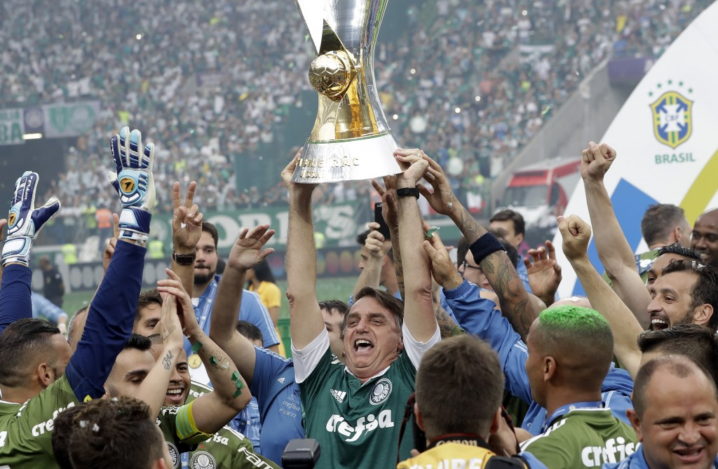 Brazil's President-elect Jair Bolsonaro holds up the national league soccer championship trophy as he celebrates with the Palmeiras soccer club in Sao