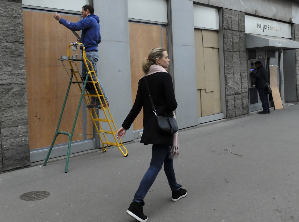 A woman walks past a worker fixing wooden pieces on a bank window near the Champs-Elysees avenue, Friday, Dec. 7, 2018 in Paris. Drastic security meas