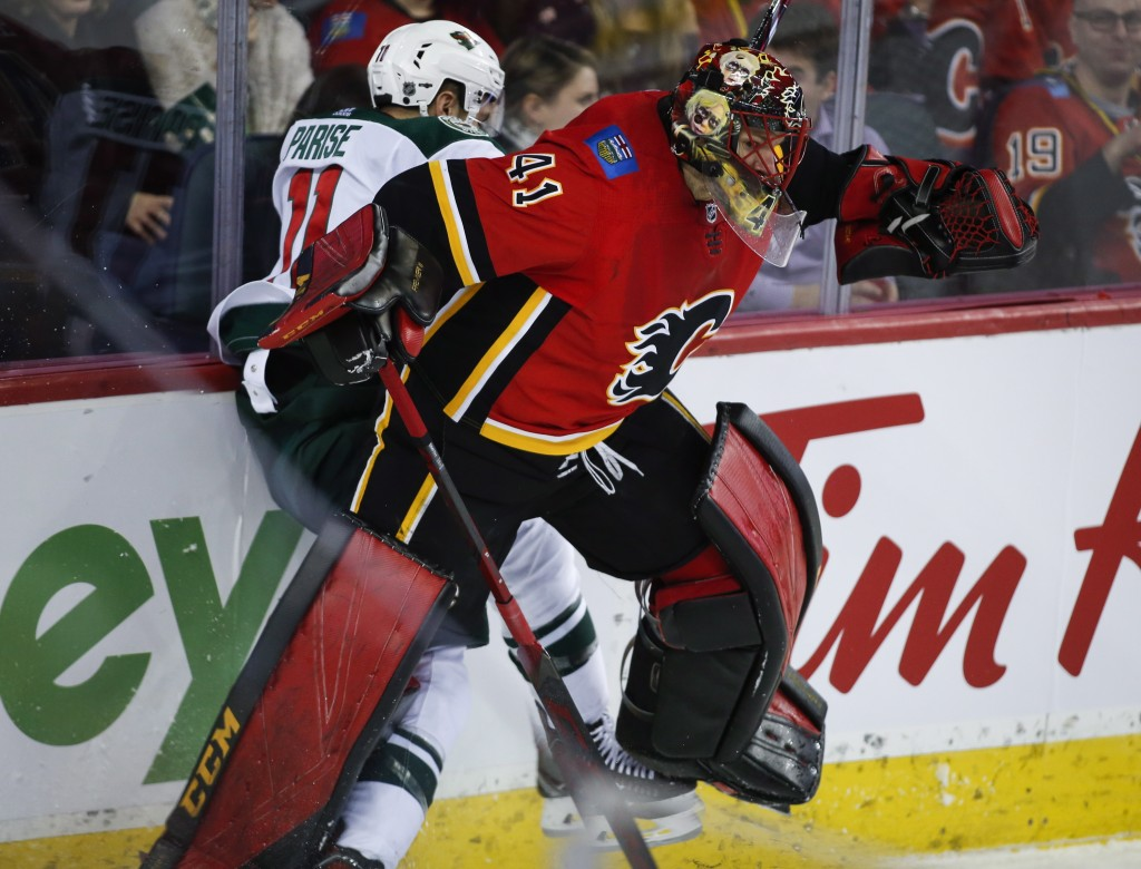 Minnesota Wild's Zach Parise, left, is checked by Calgary Flames goalie Mike Smith during second-period NHL hockey game action in Calgary, Alberta, Th