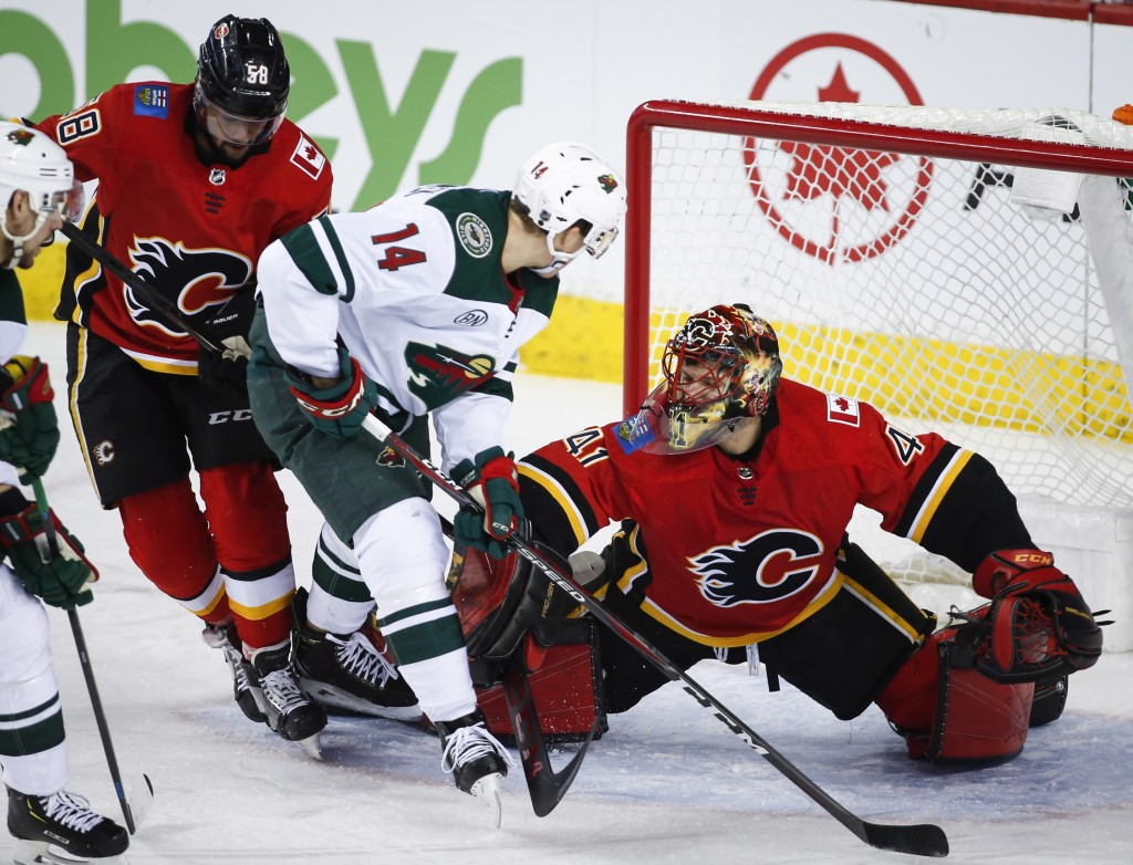 Minnesota Wild's Joel Eriksson, center, of Sweden, is shoved away from the net by Calgary Flames goalie Mike Smith, right, as Flames' Oliver Kylington