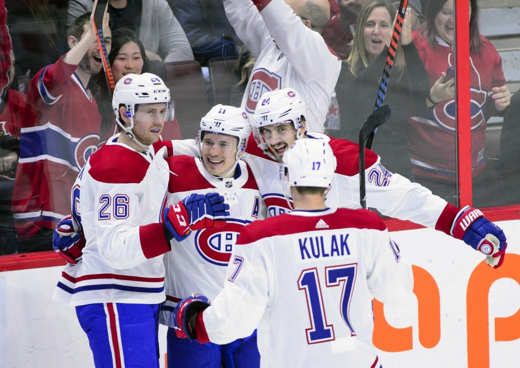 Montreal Canadiens right wing Brendan Gallagher (11), center, celebrates a goal with teammates during third-period NHL hockey game action against the