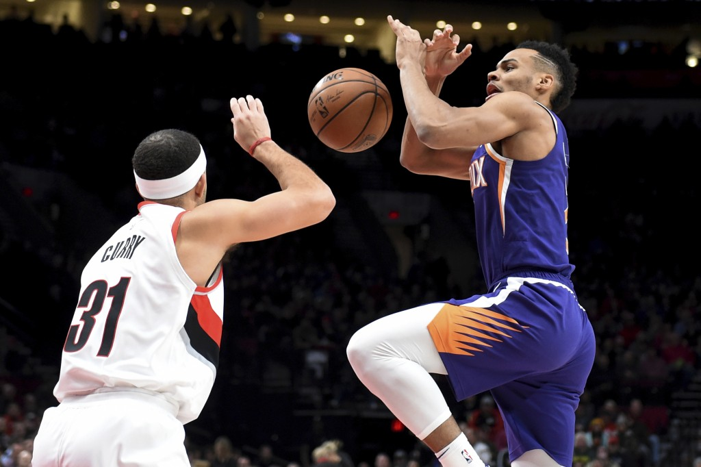 Portland Trail Blazers guard Seth Curry, left, knocks the ball away from Phoenix Suns guard Elie Okobo, right, during the first half of an NBA basketb
