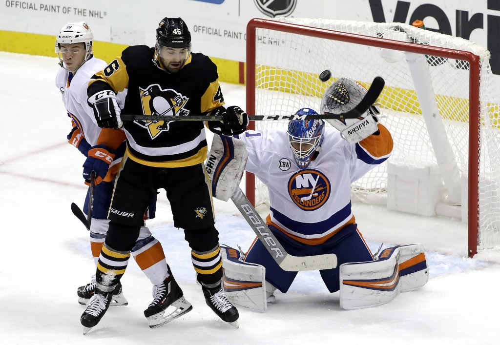 Pittsburgh Penguins' Zach Aston-Reese (46) deflects the puck over the head of New York Islanders goaltender Thomas Greiss (1) and over the goal cage w