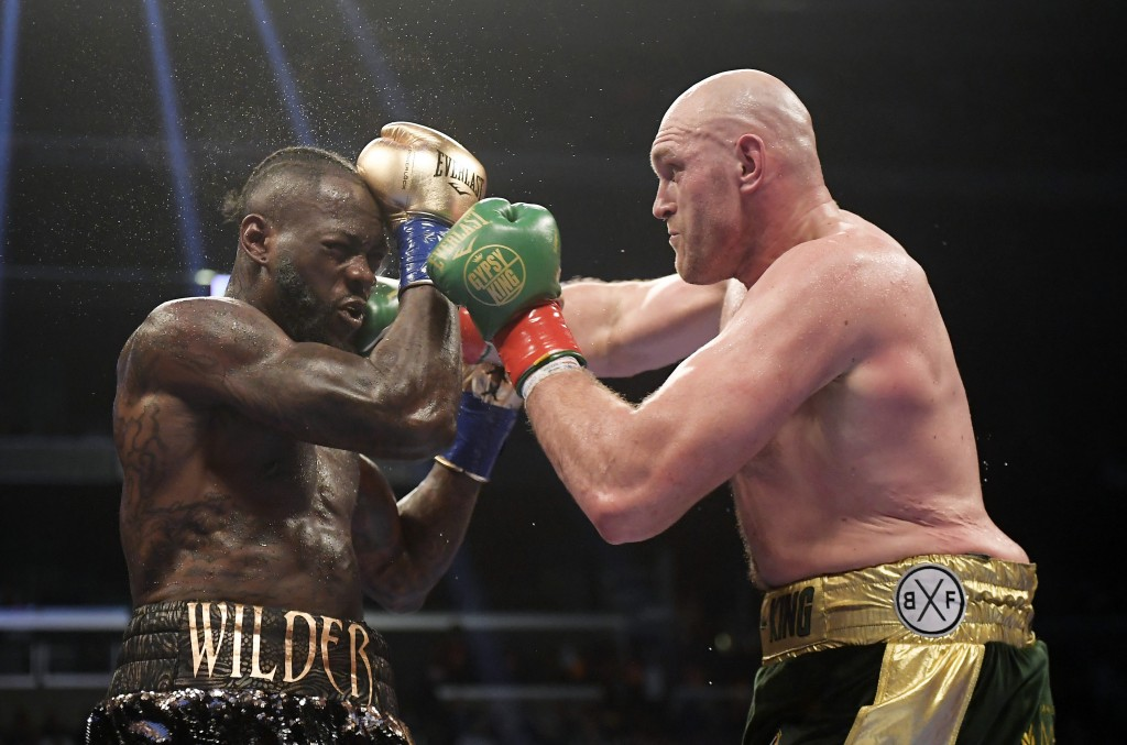 FILE - In this Dec. 1, 2018, file photo, Tyson Fury, right, of England, connects with Deontay Wilder during a WBC heavyweight championship boxing matc
