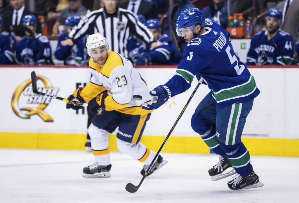 Vancouver Canucks' Derrick Pouliot (5) reaches for the puck in front of Nashville Predators' Rocco Grimaldi (23) during the first period of an NHL hoc