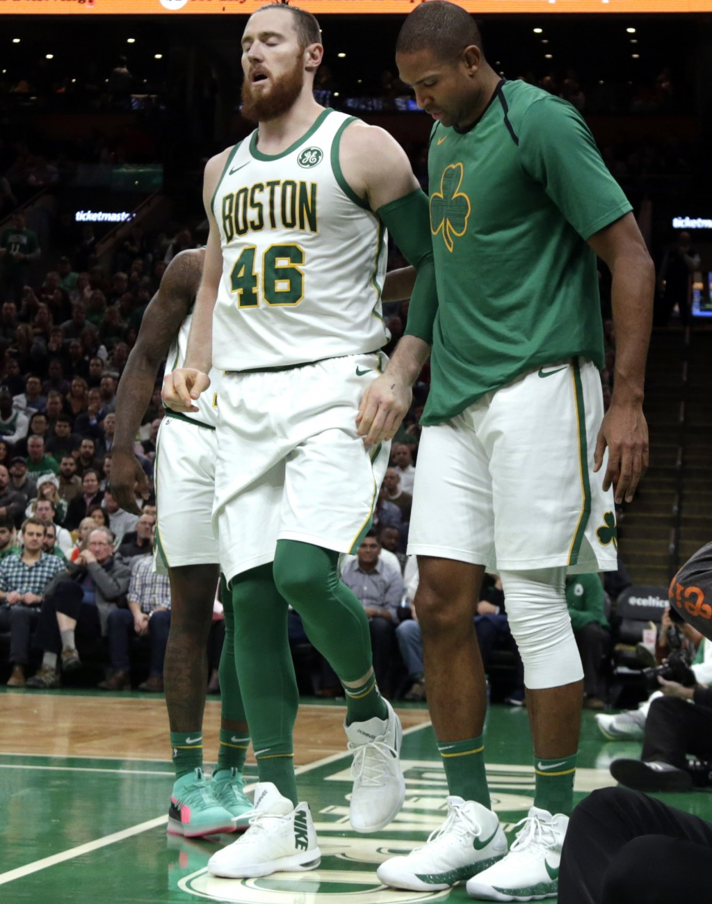 Boston Celtics center Aron Baynes (46) limps off the court with an injury as teammate Al Horford, right, walks with him in the first quarter of an NBA