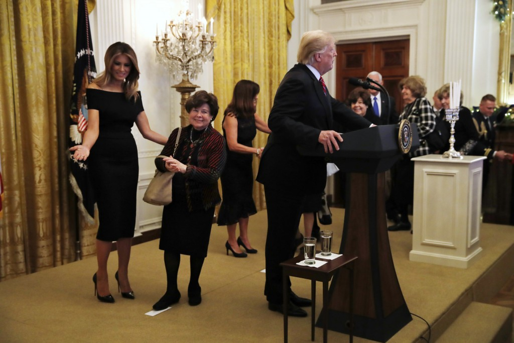 First lady Melania Trump, left, and Karen Pence, wife of Vice President Mike Pence, center, welcome Holocaust survivors to the stage as President Dona