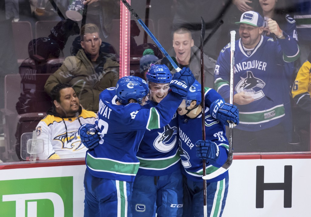 Vancouver Canucks' Bo Horvat, Jake Virtanen and Antoine Roussel, of France, from left, celebrate Virtanen's goal against the Nashville Predators durin