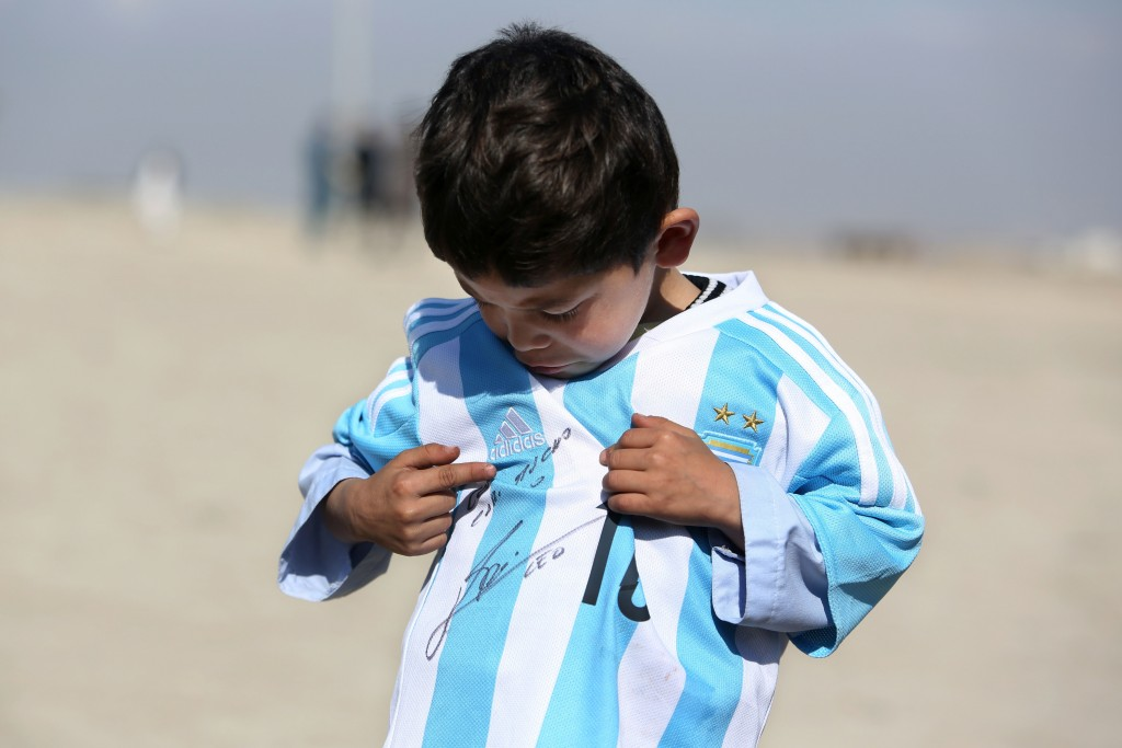 FILE - In this Friday, Feb. 26, 2016 file photo, five-year-old Afghan Lionel Messi fan Murtaza Ahmadi poses for photograph, as he wears a shirt signed