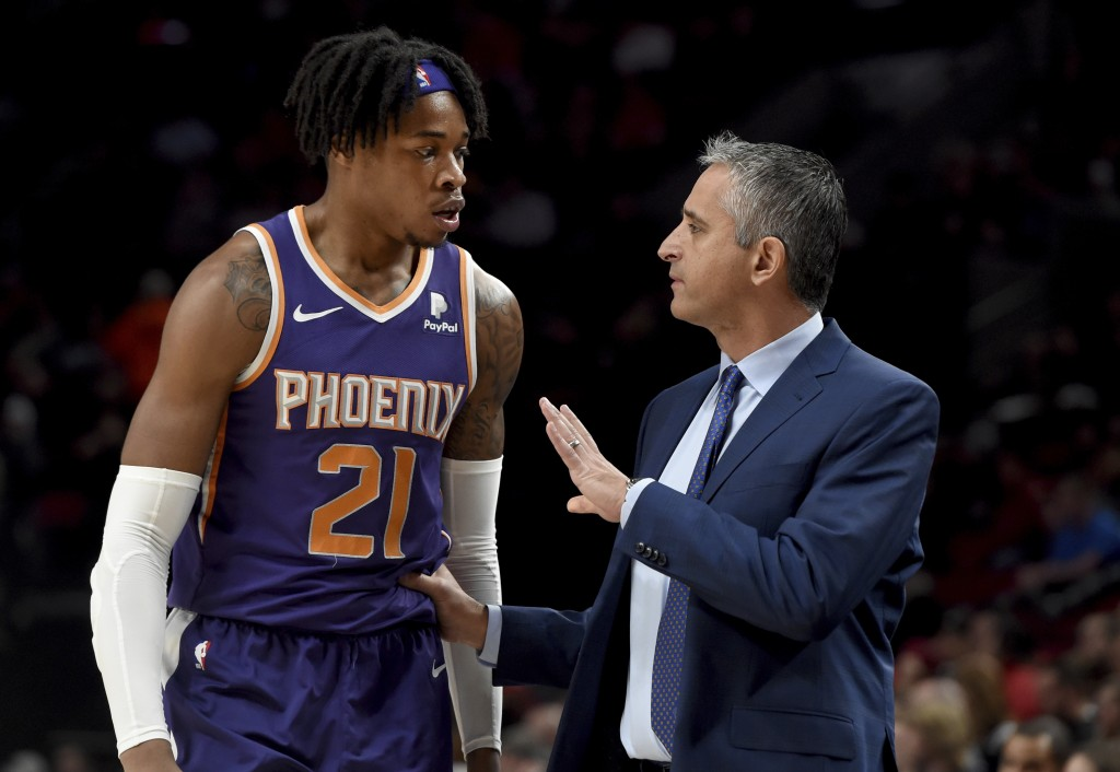 Phoenix Suns forward Richaun Holmes, left, speaks with head coach Igor Kokoskov, right, during the first half of an NBA basketball game against the Po